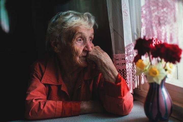 Uma senhora idosa sentada perto duma janela, olhando para fora.