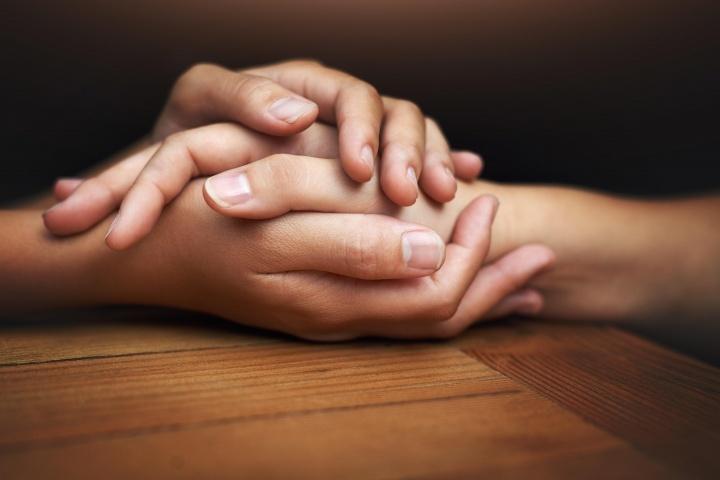 Mãos de duas pessoas tocando e demonstrando conforto.
