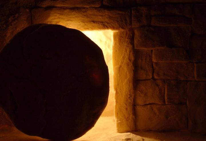 Pedra redonda em frente a um túmulo.
