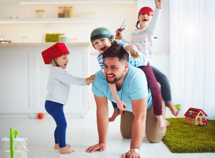 Um pai brincando com seus filhos.