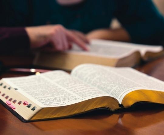 Bíblias abertas sobre uma mesa.